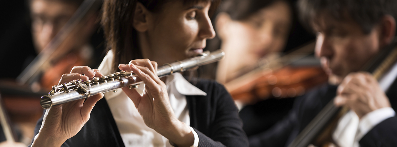 Female flutist close-up with orchestra performing in background