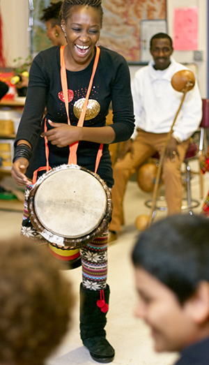 African drummer playing in a school classroom