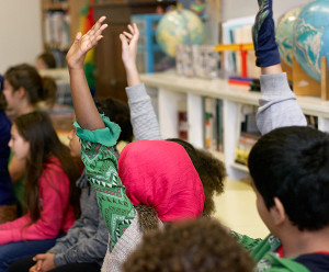 Students raising hands in a classroom